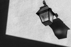 Lamppost on the wall with shadows and textures. Black and White Stock Images