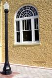Lamppost y ventana negros contra la pared amarilla del estuco Imagenes de archivo