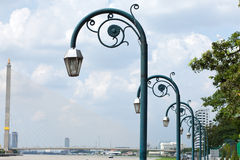 Lamps arranged in a row. Behind a bridge crossing the river Royalty Free Stock Photo