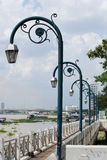 Lamps arranged in a row. Behind a bridge crossing the river Royalty Free Stock Photography
