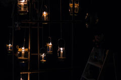 Lamps with candles are  hanging  on a tree at night. Wedding nig Stock Photos