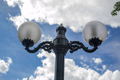 Lamps in a cloudy sky. A pair of lamps with a blue cloudy sky as background royalty free stock images
