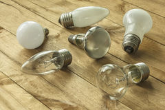 Lamps with different cap lie on a wooden surface Stock Image