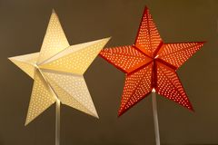 Lamps in the form of a star with holes on a pole of yellow red color on a background of brown color. Christmas, New year, design
