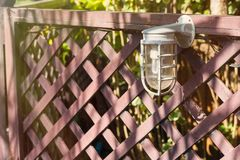 Lamps for illumination on a wooden fence in the garden. Lamps for illumination on a wooden fence in the garden Stock Photo