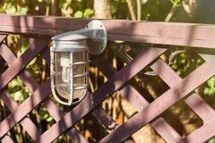 Lamps for illumination on a wooden fence in the garden. Lamps for illumination on a wooden fence in the garden Royalty Free Stock Photos