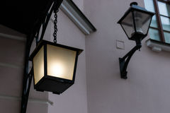 Lamps lighted and switched off. Outside lamp hangs on a chain and is lighted. Another lamp is fixed to the building wall and is switched off. Details of Stock Image