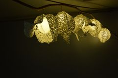 The lamps made of paper have hollow patterns. 5 lamps made of paper have hollow patterns. They are hung on branches, ranging from big to small, with yellowish stock image