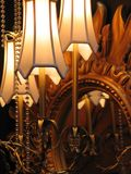 Lamps and mirror. Lamps with white glass lamp-shades near the mirror with carved wooden frame Stock Photos