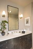 Lamps By Mirror Over Washbasin In Bathroom Stock Photos