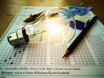 Lamps and stationery placed in the answer sheet with educational concepts royalty free stock photo