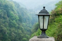 Lamp. Vintage road lamp on stone,background is mountain Royalty Free Stock Photography