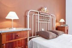 Lampskärmar nära den gamla klassiska sängen i sovrummet. royaltyfri fotografi