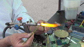Lampworking. The artist makes jewelry. stock footage