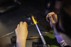 Lampworking - konstnärlig behandling av exponeringsglas i flamman Kvinnamor Arkivfoto