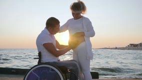 Lamslagen förälskelse, gravid kvinnlig med den ogiltiga maken i rullstol på solnedgången, lager videofilmer