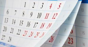Lançamento de três folhas do calendário com números pretos e vermelhos Foto de Stock