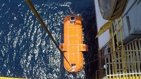 Lançamento do barco salva-vidas no mar dos moluscos na plataforma a pouca distância do mar filme