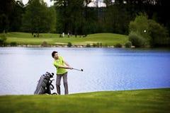 Lançamento do jogador de golfe no lago imagens de stock