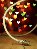 LAN cable on a background of hearts. Stock Images
