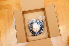 LAN cable in cardboard box. FTP CAT6a Black digital computer cable ethernet rj45 on top of e-commerce cardboard box after unboxing royalty free stock photos