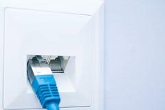 LAN-kabel pluggade in i vägguttaget Royaltyfri Bild