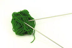 Lana verde con le paia dei ferri da maglia Fotografie Stock