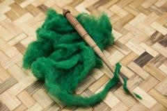 Lana verde e vecchio primo piano del fuso su fondo di legno Strumenti per tricottare della lana Fotografia Stock