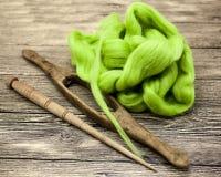 Lana verde e vecchio primo piano del fuso su fondo di legno Strumenti per tricottare della lana Immagine Stock Libera da Diritti