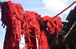 Lanas coloreadas rojo intenso que cuelgan para secarse foto de archivo libre de regalías