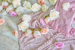 Lanas que hacen punto rosadas con las flores en una textura de madera Imagen de archivo libre de regalías