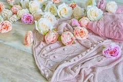 Lanas que hacen punto rosadas con las flores en una textura de madera Imagenes de archivo