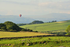 Lancashire hills, hot air balloon. A late evening balloon makes its way over Littledale, in the Lancashire hills. The hills of Yorkshire are in the distance. A Royalty Free Stock Image