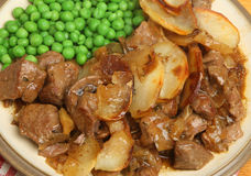 Lancashire Hotpot Dinner. Lancashire hotpot lamb stew served with peas Royalty Free Stock Image