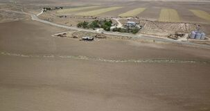 Aerial of a barn in open flat field in Lancaster, CA. Trackers and debris