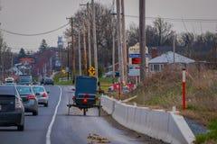 LANCASTER, EUA - ABRIL, 18, 2018: Ideia exterior da parte traseira do carrinho antiquado de Amish com uma equitação em urbano Foto de Stock Royalty Free