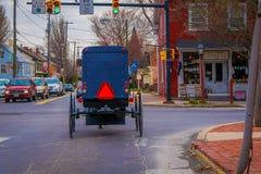 LANCASTER, EUA - ABRIL, 18, 2018: Ideia exterior da parte traseira do carrinho antiquado de Amish com uma equitação em urbano Imagem de Stock