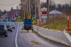 LANCASTER, EUA - ABRIL, 18, 2018: Ideia exterior da parte traseira do carrinho antiquado de Amish com uma equitação em urbano Imagem de Stock Royalty Free