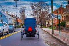 LANCASTER, EUA - ABRIL, 18, 2018: Ideia exterior da parte traseira do carrinho antiquado de Amish com uma equitação em urbano Fotos de Stock Royalty Free