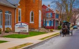 LANCASTER, EUA - ABRIL, 18, 2018: Vista do carrinho antiquado de Amish com uma equitação nas ruas na rua urbana imagens de stock royalty free