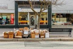 LANCASTER, PENNSYLVANIA - 4. APRIL 2018: Einige Hartfaserplattenpapierkästen verlassen auf Seite der Straße stockbild