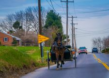 LANCASTER, USA - APRIL, 18, 2018: Outdoor view of Amish horse and carriage travels on a road. With yellow sign at one side of the road, with some cars behind Stock Photos