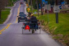 LANCASTER, USA - APRIL, 18, 2018: Outdoor view of Amish horse and carriage travels on urban road, in the town of. Lancaster, in Penssylvania Stock Photo