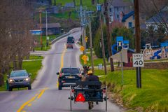 LANCASTER, USA - APRIL, 18, 2018: Outdoor view of Amish horse and carriage travels on urban road, in the town of. Lancaster, in Penssylvania Royalty Free Stock Photos