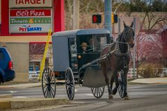 LANCASTER, USA - APRIL, 18, 2018: View of amish carriage along the city, known for simple living with touch of nature. Contacy, plain dress, and reluctance to Stock Photo