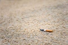 Lance do topo do cigarro na areia pelo ser humano na praia é causa do lixo no oceano e na poluição ambiental foto de stock royalty free