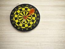 Lance la flecha y la diana en fondo de madera marrón imagen de archivo libre de regalías