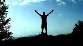 Lanceert de silhouet jonge mens tot bovenkant van berg en tilt zijn handen als teken van voltooiing, succes en vreugde op Concept stock videobeelden