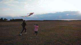 Lancement heureux de fille de m?re et d'enfant de famille un cerf-volant sur le pr? au coucher du soleil Temps dr?le de famille C banque de vidéos