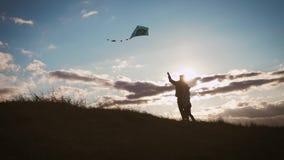 Lancement heureux de fille de père et d'enfant de famille un cerf-volant sur le pré au coucher du soleil Temps drôle de famille C clips vidéos